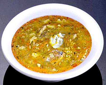 Суп рассольник с перловкой и солеными огурцами в тарелке