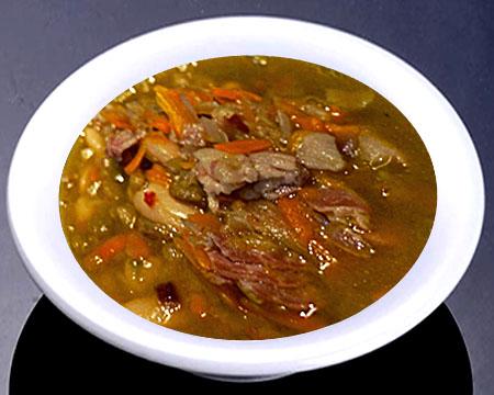 Суп из чечевицы с беконом в тарелке