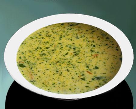 Сырный суп с зеленью в тарелке