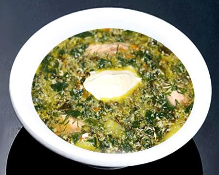 Зеленый борщ на курином бульоне в тарелке